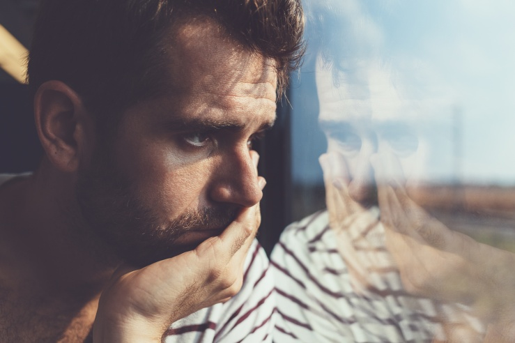 Depressed man looking out a window