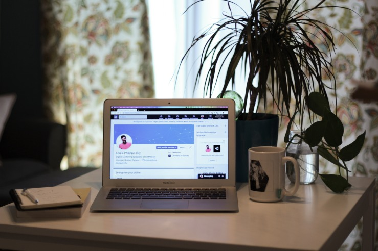 A dining room scene with a laptop showing LinkedIn. It depicts a job hunting scenario.